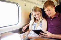 Pares jovenes que leen un libro en viaje de tren Imágenes de archivo libres de regalías