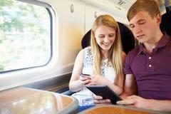 Pares jovenes que leen un libro en viaje de tren Foto de archivo libre de regalías