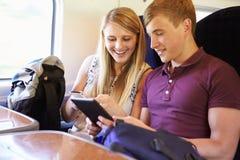 Pares jovenes que leen un libro en viaje de tren Foto de archivo