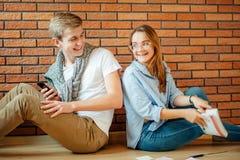 Pares jovenes que leen un libro que se sienta en piso de madera en casa Fotos de archivo libres de regalías