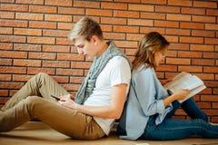 Pares jovenes que leen un libro que se sienta en piso de madera en casa Fotos de archivo