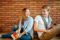 Pares jovenes que leen un libro que se sienta en piso de madera en casa Imagen de archivo