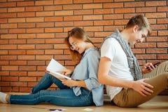 Pares jovenes que leen un libro que se sienta en piso de madera en casa Foto de archivo libre de regalías