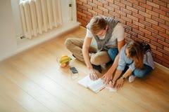 Pares jovenes que leen un libro que se sienta en piso de madera en casa Fotografía de archivo