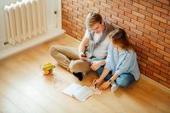 Pares jovenes que leen un libro que se sienta en piso de madera en casa Imagen de archivo libre de regalías