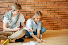 Pares jovenes que leen un libro que se sienta en piso de madera en casa Fotografía de archivo libre de regalías