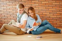 Pares jovenes que leen un libro que se sienta en piso de madera en casa Imágenes de archivo libres de regalías