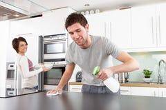 Pares jovenes que limpian la cocina moderna Imágenes de archivo libres de regalías