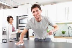 Pares jovenes que limpian la cocina moderna Fotos de archivo