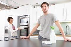 Pares jovenes que limpian la cocina moderna Foto de archivo libre de regalías