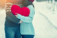 Pares jovenes que llevan a cabo el corazón rojo grande foto de archivo libre de regalías