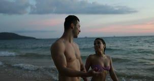 Pares jovenes que llevan a cabo las manos que caminan en la playa en los turistas que hablan crepusculares hombre y mujer junto e almacen de video