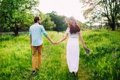 Pares jovenes que llevan a cabo las manos que caminan a través de un prado fotos de archivo libres de regalías