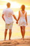 Pares jovenes que llevan a cabo las manos en la puesta del sol de la playa Fotos de archivo libres de regalías