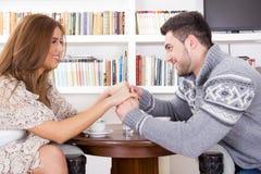 Pares jovenes que llevan a cabo las manos en la sala de estar Foto de archivo
