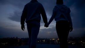 Pares jovenes que llevan a cabo las manos, fecha romántica en el tejado, fechando el lugar, relación fotos de archivo libres de regalías
