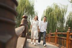 Pares jovenes que llevan a cabo las manos y que cruzan un puente Imagen de archivo libre de regalías
