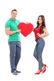 Pares jovenes que llevan a cabo un corazón rojo grande Fotografía de archivo libre de regalías