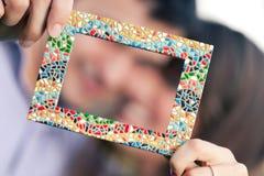 Pares jovenes que llevan a cabo un marco de la foto, marco aislado imagen de archivo
