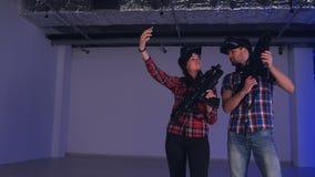 Pares jovenes que llevan los vidrios y los armas de la realidad virtual que toman selfies en el teléfono almacen de video