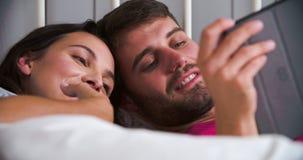 Pares jovenes que mienten en cama usando la tableta de Digitaces almacen de metraje de vídeo