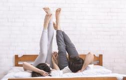 Pares jovenes que mienten en cama y que aumentan las piernas en aire imágenes de archivo libres de regalías
