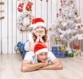 Pares jovenes que mienten en el piso del sitio adornado de la Navidad Fotos de archivo
