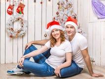 Pares jovenes que mienten en el piso del sitio adornado de la Navidad Foto de archivo