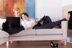 Pares jovenes que mienten en el sofá Imagen de archivo