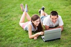 Pares jovenes que mienten en hierba con la computadora portátil Imagen de archivo
