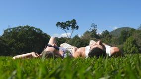 Pares jovenes que mienten en hierba verde en parque y que se relajan Hombre y mujer que se sientan en prado en la naturaleza Mira Imagen de archivo
