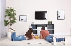 Pares jovenes que mienten en la alfombra y la TV de observación fotografía de archivo libre de regalías
