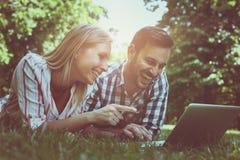Pares jovenes que mienten en la hierba Pares felices usando la computadora portátil fotos de archivo