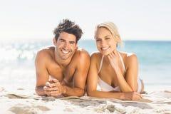 Pares jovenes que mienten en la playa Fotos de archivo