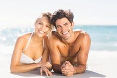 Pares jovenes que mienten en la playa Imágenes de archivo libres de regalías