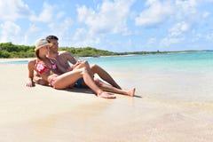 Pares jovenes que mienten en la playa en las islas caribeñas Imagen de archivo libre de regalías