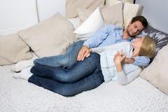 Pares jovenes que mienten en un sofá Fotos de archivo