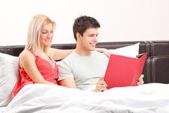 Pares jovenes que mienten en una cama y que leen un libro Imagen de archivo libre de regalías