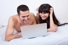 Pares jovenes que mienten para arriba en cama con la computadora portátil Imagen de archivo libre de regalías