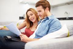 Pares jovenes que miran con finanzas personales en casa Imagen de archivo