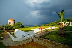 Pares jovenes que miran el cielo de la tormenta con un arco iris hermoso sobre el mar en un hotel griego fotos de archivo libres de regalías