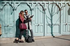 Pares jovenes que miran el libro en la calle imágenes de archivo libres de regalías