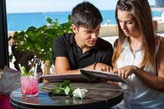 Pares jovenes que miran el menú en restaurante. Imagen de archivo libre de regalías