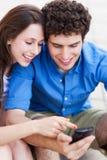 Pares jovenes que miran el teléfono móvil Imagen de archivo libre de regalías