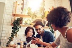 Pares jovenes que miran el teléfono elegante mientras que se sienta en café Foto de archivo