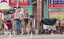 Pares jovenes que miran en línea el patinaje, Pekín, China Imagenes de archivo