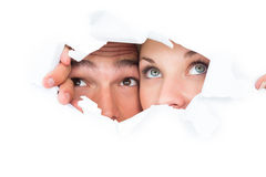 Pares jovenes que miran a escondidas a través del papel rasgado Fotos de archivo libres de regalías