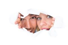 Pares jovenes que miran a escondidas a través del papel rasgado Imagen de archivo