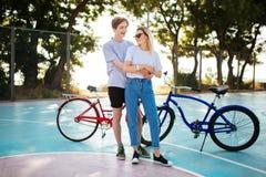 Pares jovenes que miran feliz en uno a con las bicicletas rojas y azules en fondo Muchacho alegre que se coloca con hermoso Foto de archivo