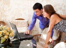 Pares jovenes que miran la computadora portátil Fotografía de archivo libre de regalías